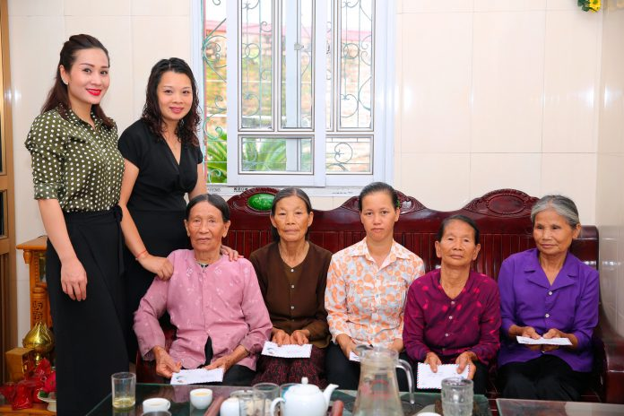 Hoa hậu Vũ Loan (bìa trái) trao quà thiện nguyện cho các mẹ