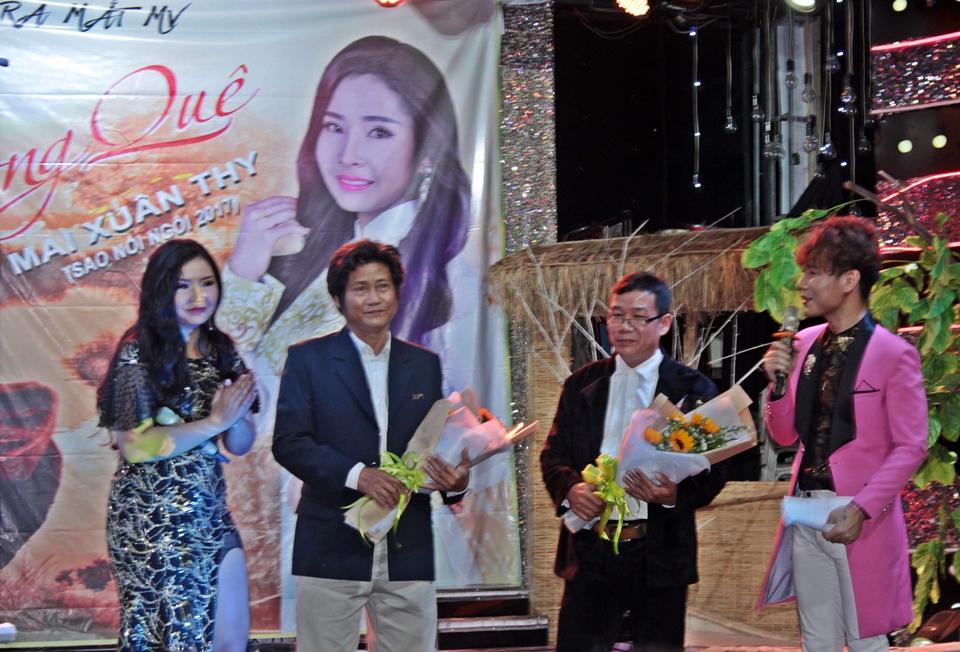 Mai Xuân Thy tặng hoa cám ơn thầy Song Thi (thứ 2 từ trái sang) và cha - nghệ sĩ, soạn giả Chánh Linh trong buổi ra mắt MV Vọng quê