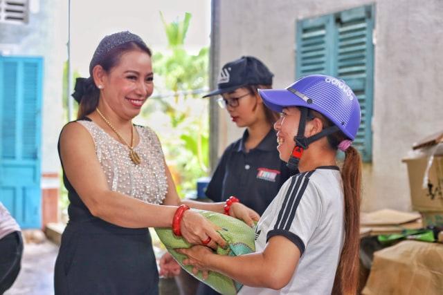 Hoa hậu Thanh Thúy cười rạng rỡ phát gạo cho bà con