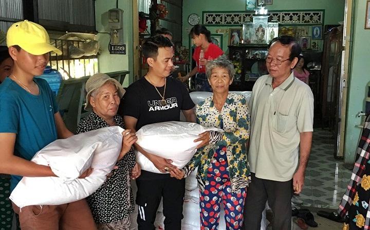 Võ Hoàng Lâm (giữa) đang phát gạo cho bà con nghèo